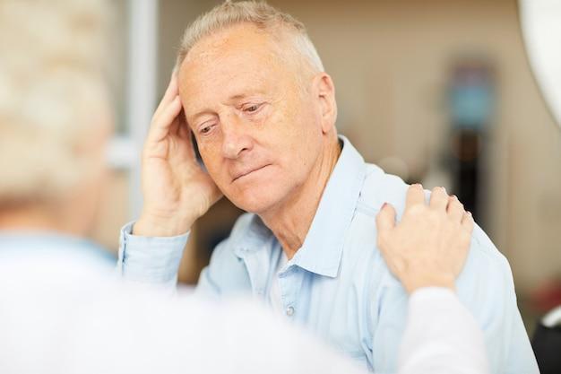 Sênior paciente ouvindo médico