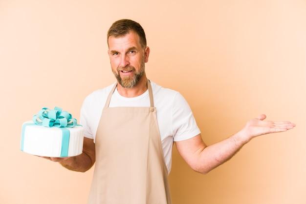 Sênior segurando um bolo isolado em um fundo bege, mostrando um espaço de cópia na palma da mão e segurando a outra mão na cintura.