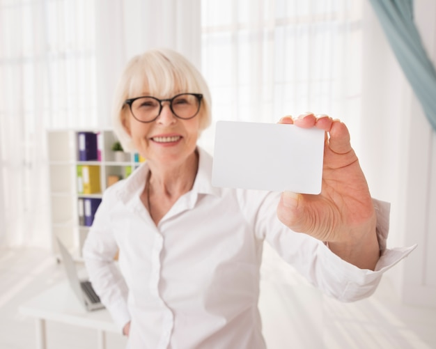 Senior, segurando um cartão de visita com espaço de cópia