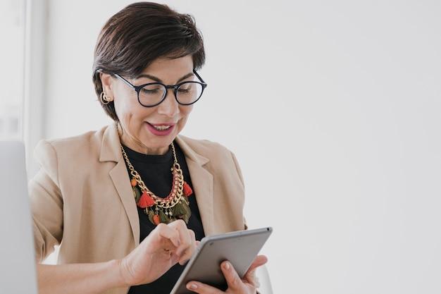 Senior, segurando um tablet com copyspce