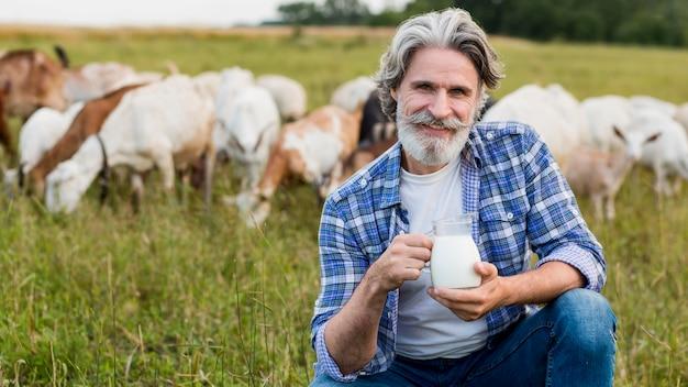 Sênior segurando uma caneca com leite de cabra