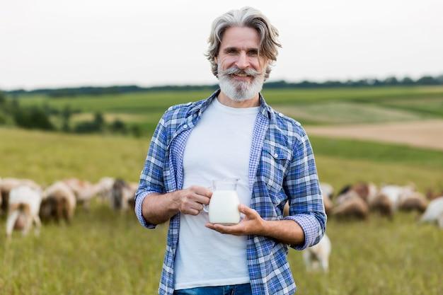 Sênior segurando uma caneca com leite