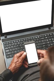 Sênior sentado em um sofá com telefone celular na mão e laptop