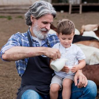 Sênior servindo leite para menino