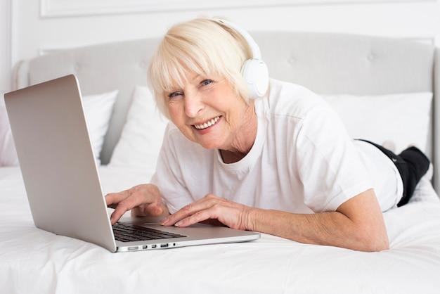 Sênior sorridente com fones de ouvido e laptop