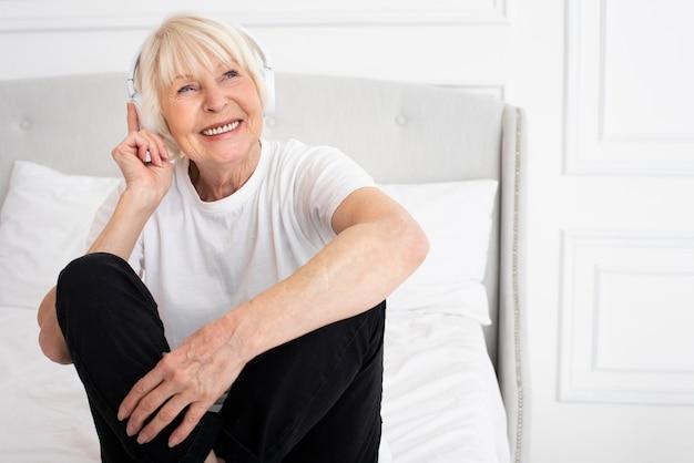 Sênior sorridente com fones de ouvido