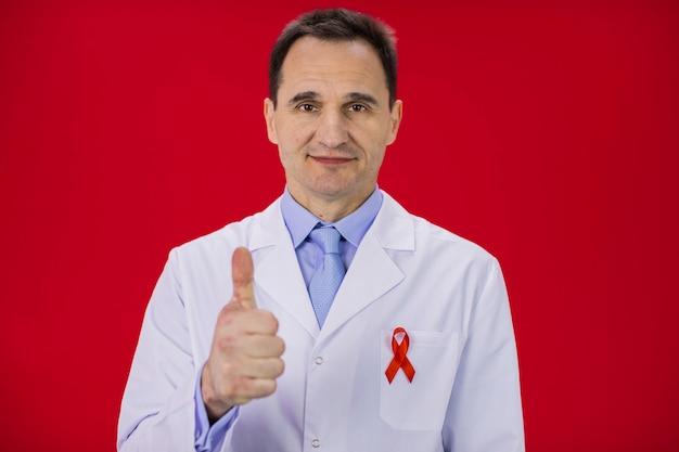 Senior sorridente médico de jaleco branco com fita vermelha mostra como sinal