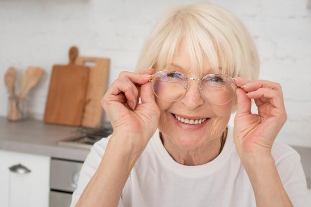 Sênior sorridente segurando um óculos