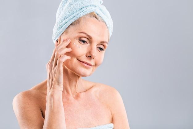 Sênior sorrindo 50 anos, mulher madura de meia-idade aplicando creme facial no rosto, olhando para a câmera, anti-idade, pele seca saudável, conceito de terapia de beleza, tratamento de pele antigo