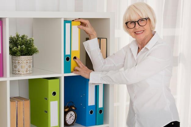 Senior tirando uma pasta do armário