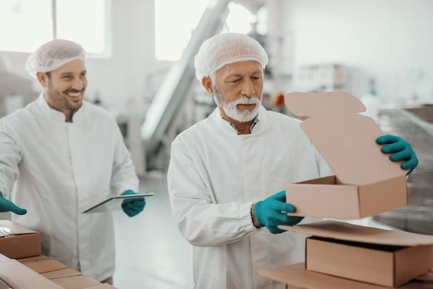 Sênior trabalhando caucasiano em uniforme branco colocando e preparando caixas enquanto sorrindo, supervisor segurando o tablet e observando-o. interior da planta alimentar.