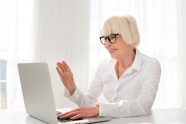 Sênior trabalhando em um laptop em seu escritório