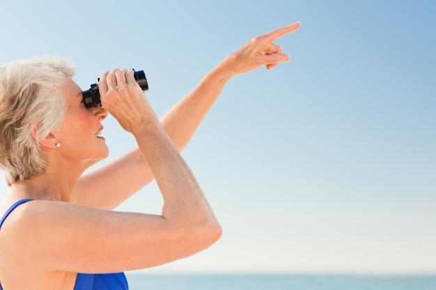 Senior woman watching bird at the beach
