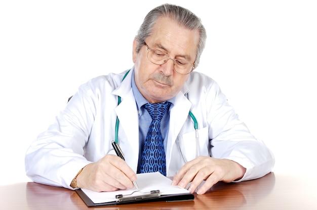 Seniors médico escrevendo um sobre fundo branco