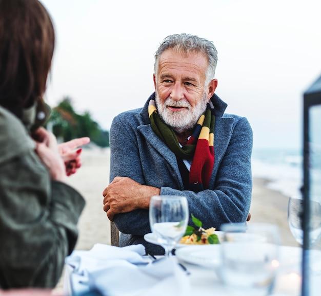 Seniors tendo um jantar na praia