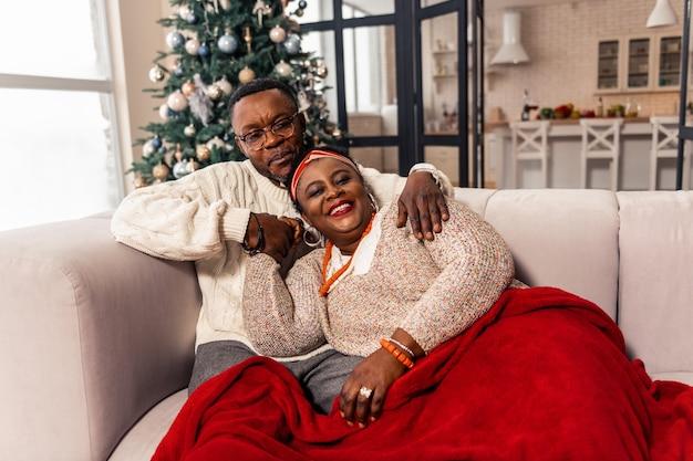 Sensação de calor. casal alegre e positivo sentindo-se aquecido enquanto é coberto por uma manta
