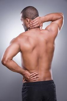 Sensação de desconforto. vista traseira de um jovem africano musculoso tocando seu quadril e pescoço