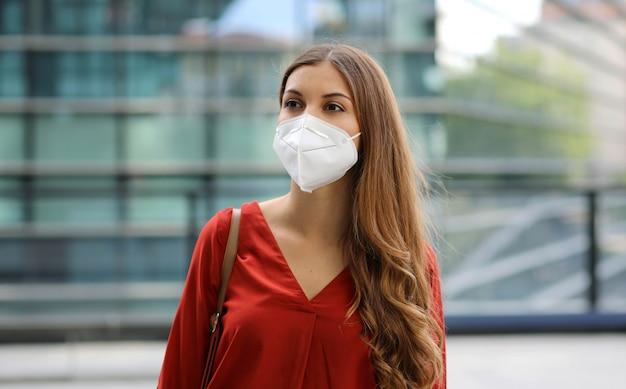 Sensação de perplexidade. mulher jovem numa rua vazia da cidade usando máscara protetora.