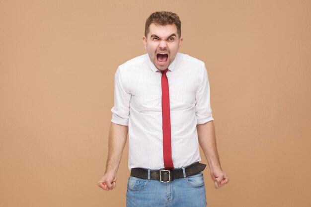 Sensação de raiva. grito do empresário. conceito de pessoas de negócios, emoções e sentimentos bons e ruins. foto de estúdio, isolada em fundo marrom claro