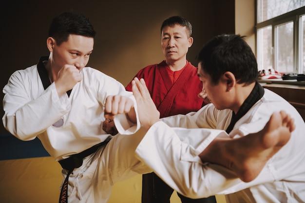 Sensei ensinando dois estudantes de artes marciais a lutar.