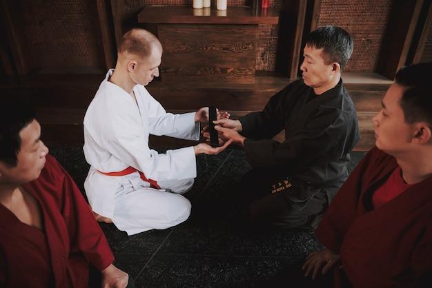 Sensei está apresentando lutador de artes marciais com faixa preta.