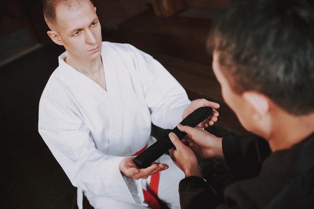 Sensei está dando faixa preta para lutador de artes marciais