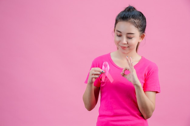 Sensibilização para o câncer de mama, mulheres vestindo camisas cor de rosa, segurando fitas cor de rosa com a mão direita a mão esquerda agiu bem, mostrando o símbolo diário contra o câncer de mama