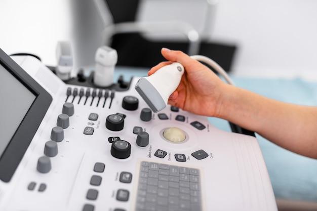 Sensor de ultrassom do scanner ultrassônico moderno nas mãos do médico jovem
