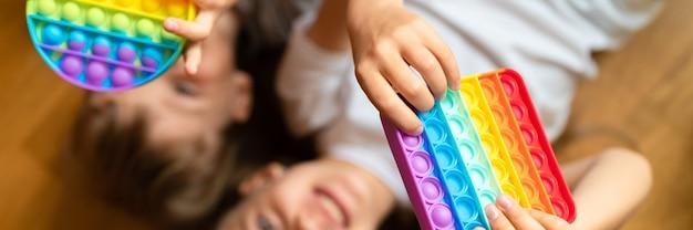 Sensorial anti-stress brinquedos pop nas mãos de uma criança. uma criancinha feliz brinca com um simples brinquedo de covinha em casa. crianças segurando e brincando com a cor do arco-íris popit, tendência de 2021 anos. bandeira