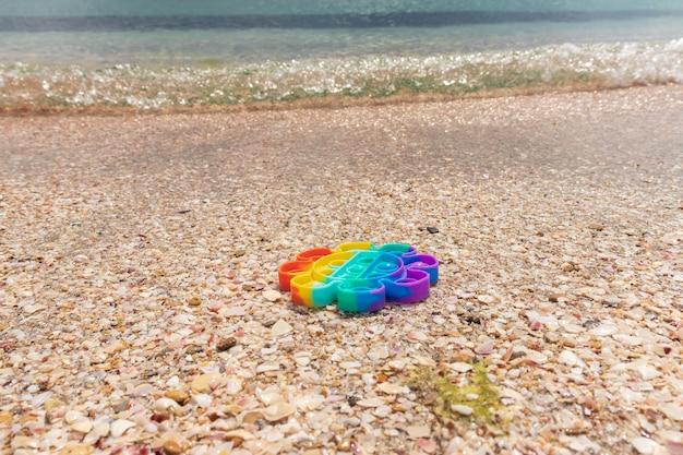 Sensorial anti-stress colorido pop-lo brinquedo na areia com água na praia. verão e relaxe o conceito. autismo precisa de brinquedo de silicone para alívio do estresse
