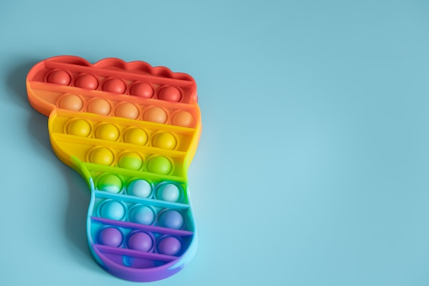 Sensorial anti-stress colorido pop-lo brinquedos em forma de pé sobre fundo azul.