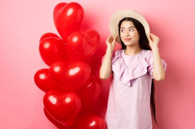 Sensual e romântica menina adolescente asiática com chapéu de palha e vestido no encontro, em pé perto de balões de coração de dia dos namorados e olhando de lado com um sorriso sonhador, fundo rosa.