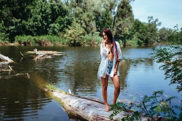 Sensual garota morena sexy em uma camisa branca desabotoada para se despir perto do rio.