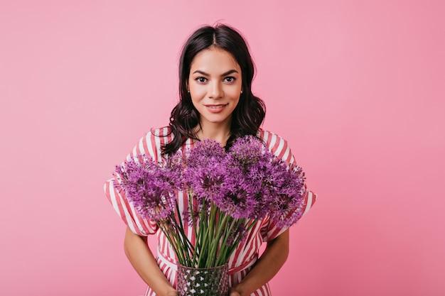 Sensual mulher com cabelo encaracolado e sorriso brilhante, posando com flores lilás.
