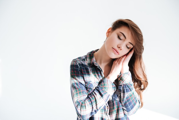 Sensual mulher jovem e atraente com os olhos fechados, tocando seu rosto