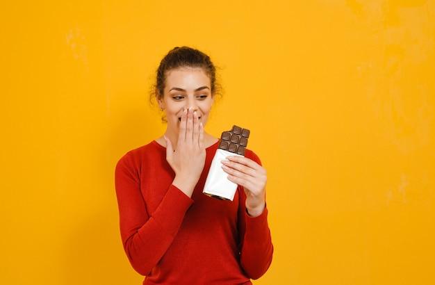 Sensual mulher jovem e atraente comendo e é espantado chocolate isolado sobre parede amarela