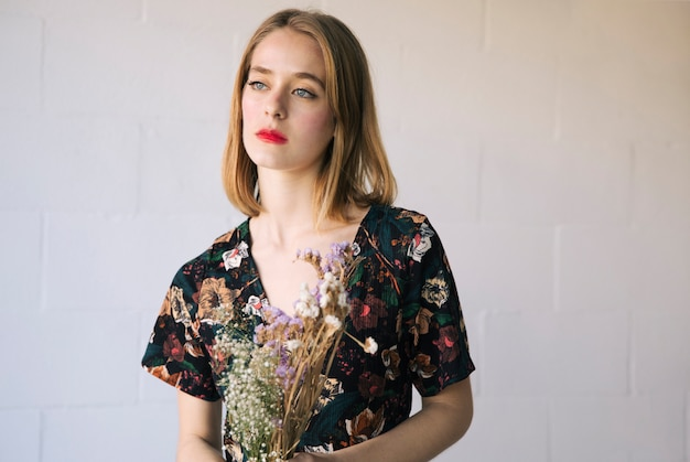 Sensual mulher pensativa com buquê de plantas secas