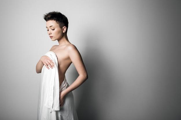 Sensual nu caucasiano mulher adulta, embrulhado em um cetim, folha de seda contra fundo cinza. alto contraste