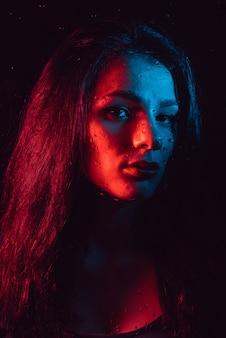 Sensual retrato de menina bonita atrás de vidro com pingos de chuva com iluminação azul vermelha