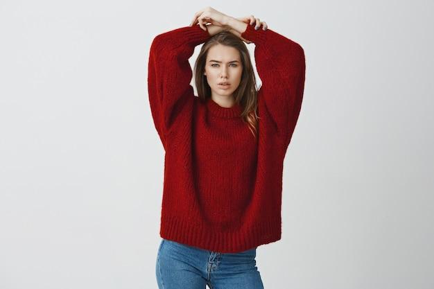 Sensualidade, beleza, conceito de cosmetologia. retrato de mulher jovem e atraente slim auto-confiante em camisola solta aconchegante vermelha, olhando de soslaio glamour arrogante, segurando as mãos relaxadas na cabeça