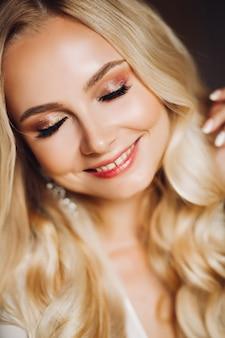 Sensualidade sorridente jovem blondie com os olhos fechados