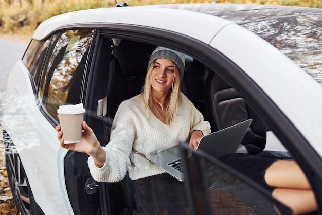 Senta-se dentro do veículo com o laptop e um copo de bebida. menina tem viagem de outono de carro. automóvel novo moderno na floresta.