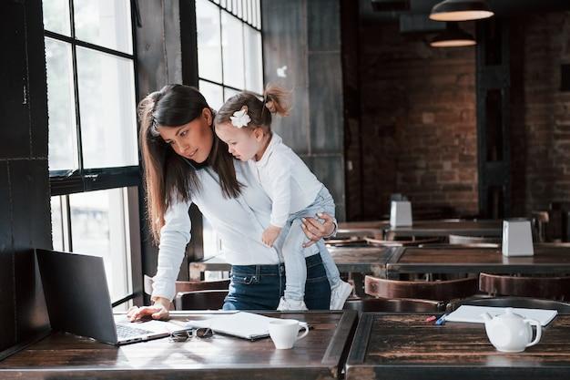 Sentado com a criança e trabalhando. mulher de negócios com roupa oficial com criança está dentro de casa no café durante o dia.