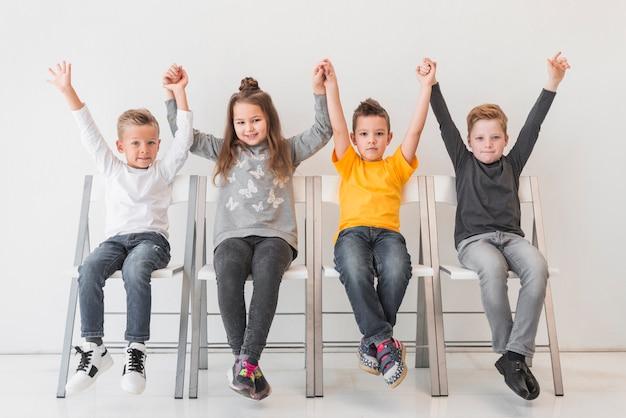 Sentado, crianças, com, seu, mãos cima