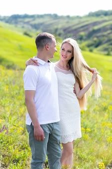 Sentado e abraçando. lindo casal jovem tem um bom tempo na floresta durante o dia.