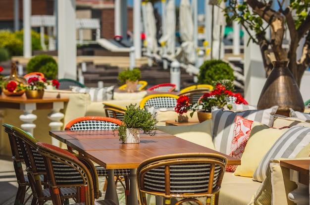 Sentado e espaço para refeições em um restaurante no terraço com móveis.