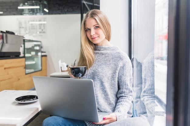 Sentado, em, café, mulher usa computador portátil, e, xícara segurando