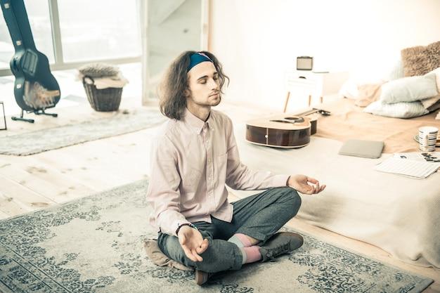 Sentado imóvel. homem calmo e estiloso sentado no tapete perto de sua cama enquanto medita e pensa sobre sua vida