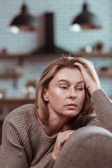 Sentado na cozinha. mulher de negócios loira sentada na cozinha de casa com alguns problemas