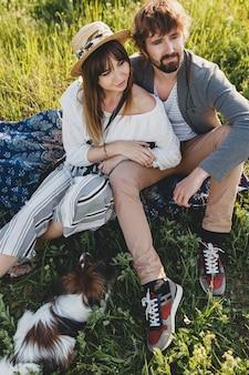 Sentado na grama, um jovem casal elegante e moderno apaixonado por um cachorro